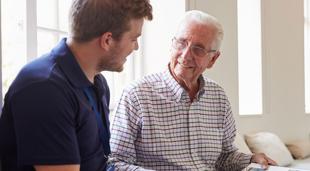 A carer listening to an older gentleman
