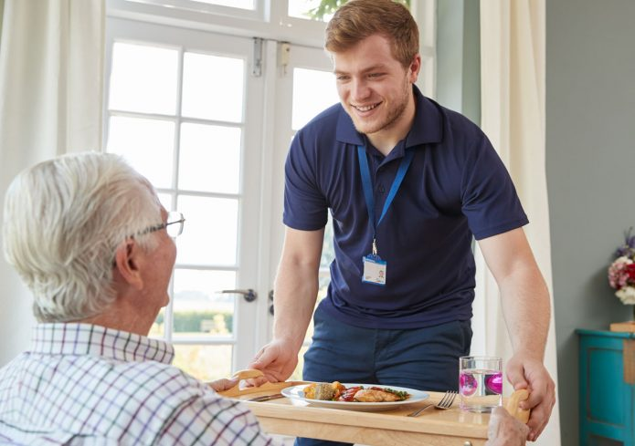 A carer passing a meal to a gentleman