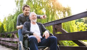 A carer taking an older gentleman outside
