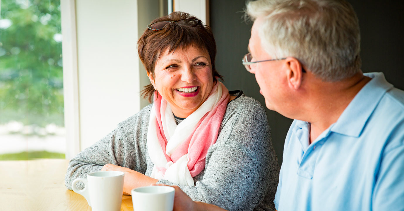 A man chatting to a lady over a coffee