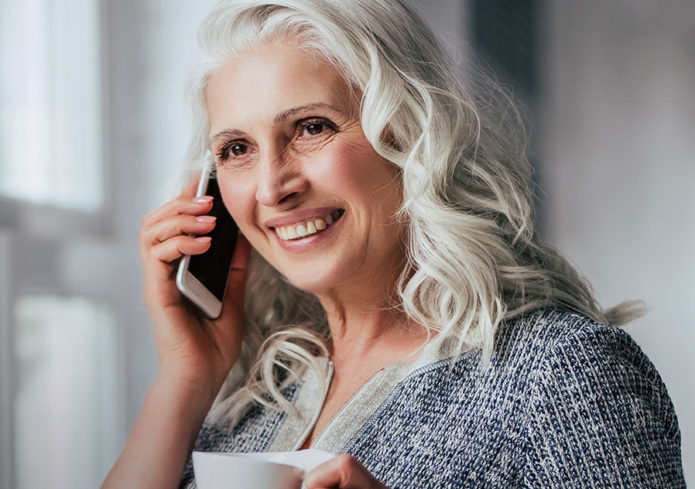 Lady smiling on the phone whilst drinking a coffee