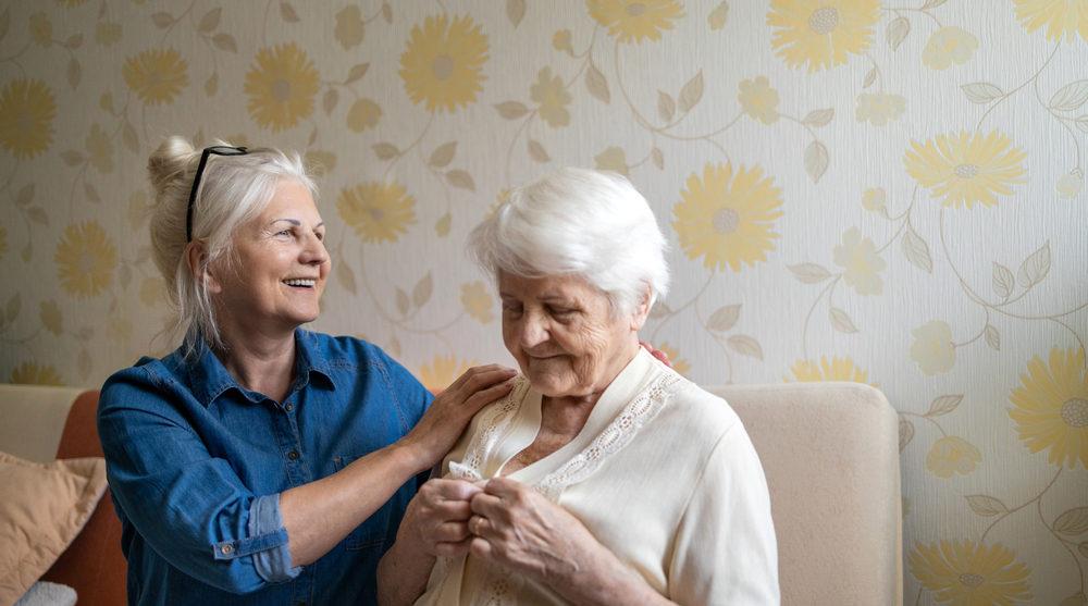 Carer helping elderly mother